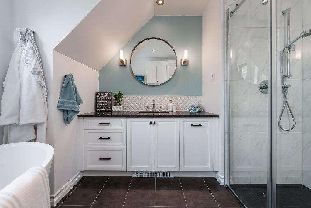 vanité sur mesure sous plafon mensardé avec miroir rond et appliqués muraux