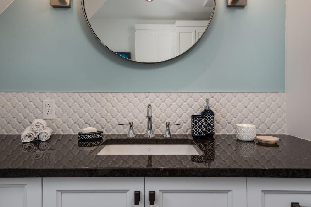 comptoir de granite avec lavabo sous-plan et robinet 3 pièces, dosseret en mosaîque blanche